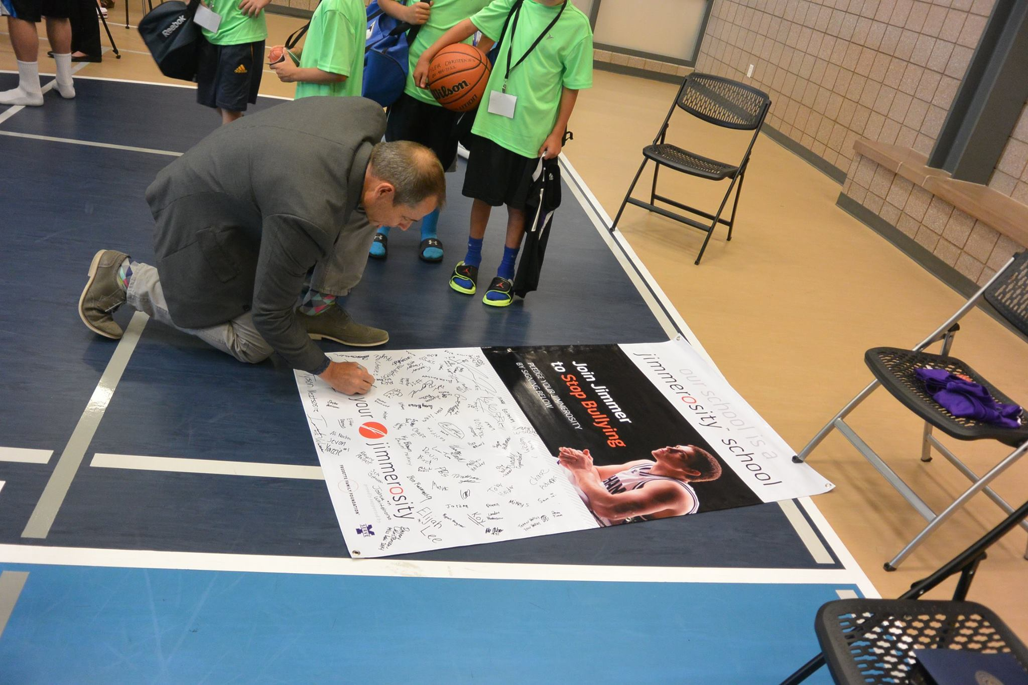 Mayor John Curtis joins the campers in signing a pledge to stand up against bullying at all times.